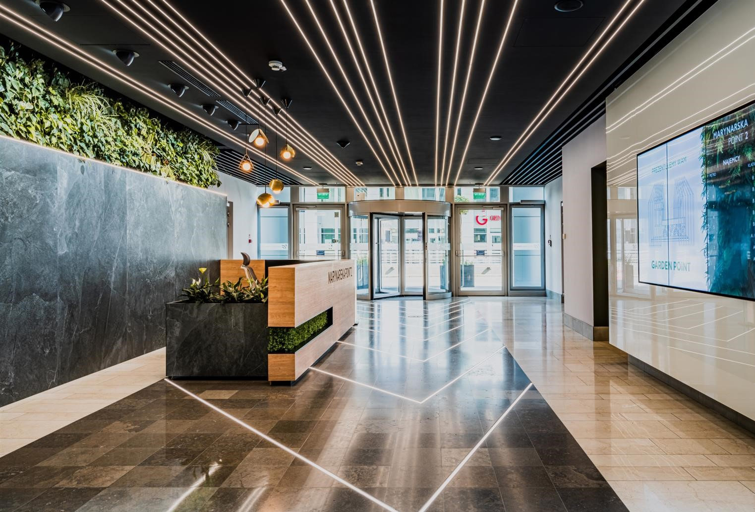 A green wall in reception welcomes visitors to Marynarska Point 2 in Warsaw, Poland
